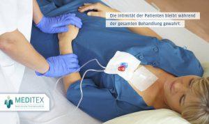 Patientin liegt im Bett. Pflegerin legt ihr einen Zugang an der Schulter und kann dies sehr gut machen, da die Patientin die medizinische Funktionswäsche trägt, die man an der Schulter oben öffnen kann.