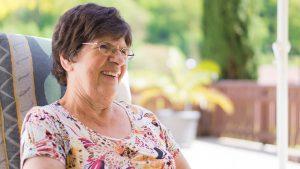 Seniorin sitz auf Terasse und lacht