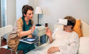 Ärztin erklärt Patientin im Krankenbett die Benutzung der VR-Brille