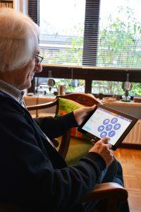 Senior sitzt zuhause vor Tablet und nutzt PAUL