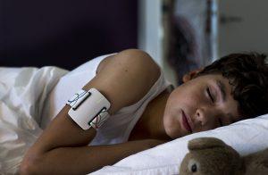 Kind schläft mit NightWatch am Arm
