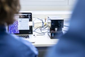 Person sitz am Laptom und betrachtet die Ergebnisse von Mimimic, einem kleinen kompakten und intelligenten trainierbaren Mikroskop zur Malaria-Diagnostik
