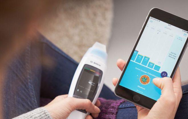 Frau hält Vivatmo me in der linken und ein Smartphone mit geöffneter Vivamot app in der rechten Hand