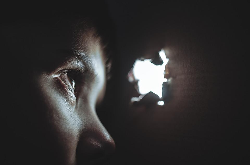 Frau blickt angstvoll durch kleines Loch