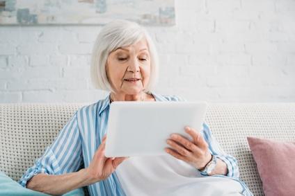 Seniorin sitzt auf Sofa und schaut auf Tablet