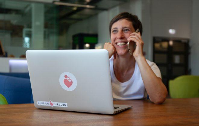 Hebamme sitzt vor Laptop und berät Eltern am Telefon - Telefonberatug