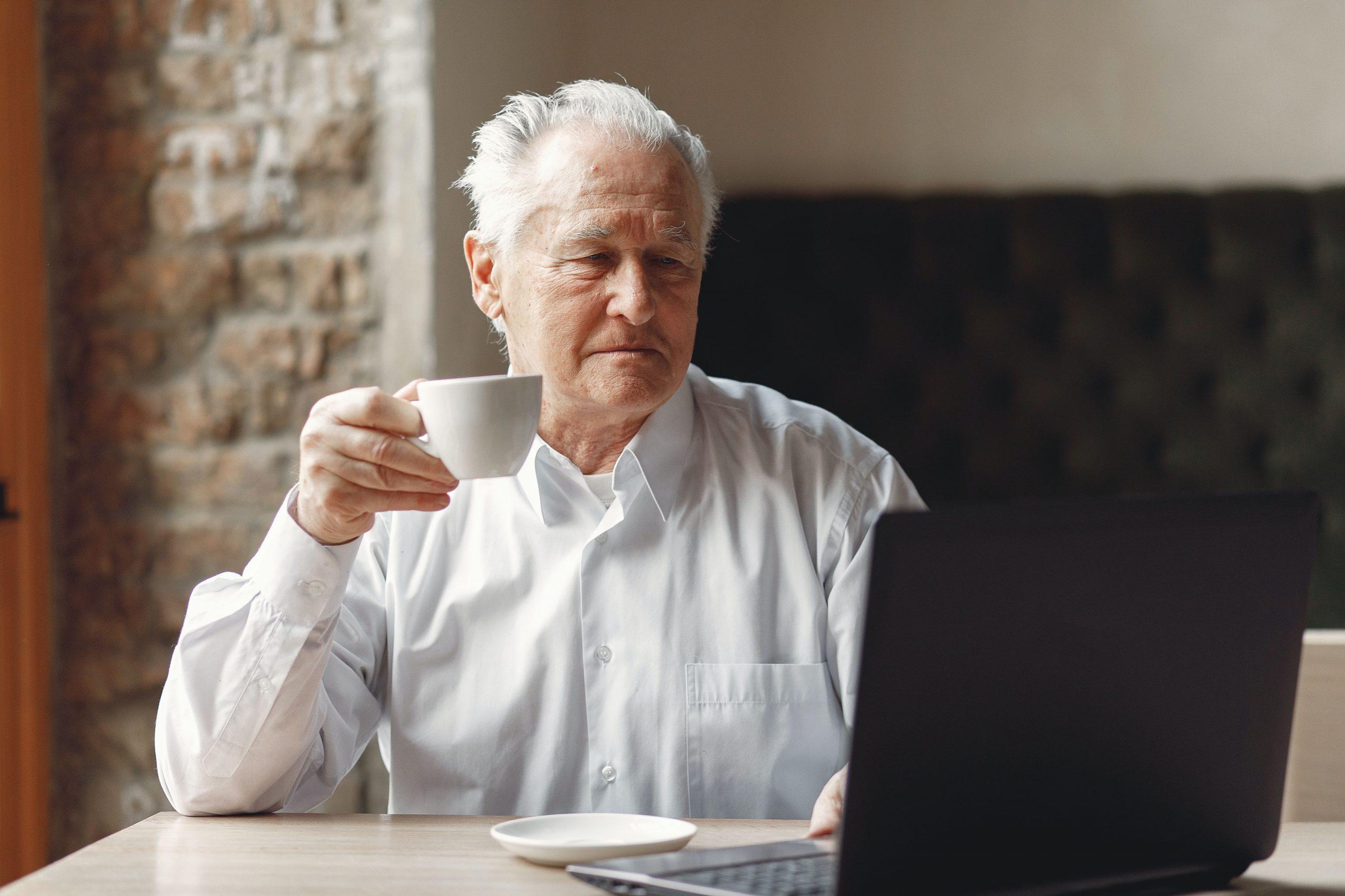 Älterer Mann sitzt vor Laptop mit Kaffetasse in Hand