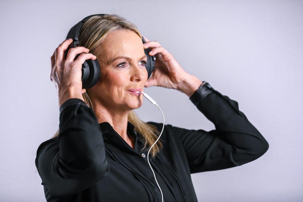 Frau mit Kopfhörern und Zungenimpulsgeber